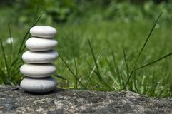 Harmony and balance, simple pebbles tower in the grass, simplicity, five stones. Harmony and balance, simple pebbles tower in the grass, simplicity still life Stock Photography
