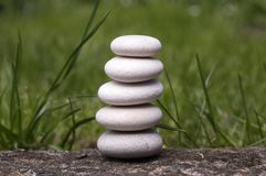 Harmony and balance, simple pebbles tower in the grass, simplicity. Still life Stock Photos