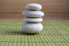 Harmony and balance, simple pebbles tower on green wooden background. Simplicity still life Stock Photography