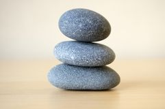 Harmony and balance, simple pebbles tower on wooden background. Harmony and balance, simple pebbles tower on light brown wooden background, simplicity still life Royalty Free Stock Photo