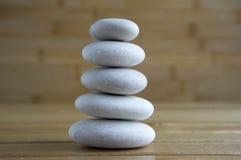 Harmony and balance, simple pebbles tower on wooden background. Harmony and balance, simple pebbles tower on light brown wooden background, simplicity still life Stock Photo