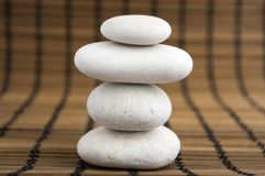 Harmony and balance, simple pebbles tower on wooden background. Harmony and balance, simple pebbles tower on light brown wooden background, simplicity still life Stock Image