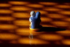 Harmony among discord. Two ceramic figures in an embrace on a small heart shaped boat amidst shadow pattern symbolizing conflict Stock Photo