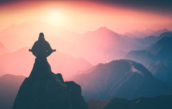 Harmony on the edge. Instagram stylisation. Silhouette of human meditating in sitting yoga position on the top of mountain above the misty valley. Zen Stock Photography