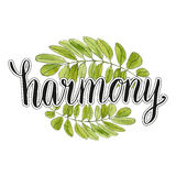 Harmony handwriting lettering with watercolor leaves background Royalty Free Stock Photo