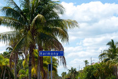 Harmony Lane street sign. A blue street sign for harmony lane is the mani focus of this tropical scene from Bonita Springs, Florida, showing palm trees and blue Royalty Free Stock Images