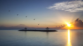 Harmony of life. The morning Sun rays warmth up the air of Sanur Beach and Mount Agung in Bali, Indonesia Royalty Free Stock Photos