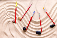 Harmony and music at the beach. With an artistic conceptual image of a wavy score drawn in golden sand with a treble clef and musical notes of smooth pebbles Stock Photos