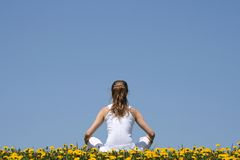 In harmony with nature. Young woman in white clothes sitting in a flowering dandelion field Royalty Free Stock Photos