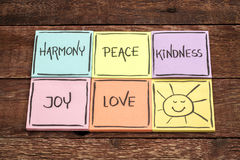 Harmony, peace, kindness, joy and love. With sun smiley -  set of sticky notes with inspirational words against rustic wood Royalty Free Stock Photos