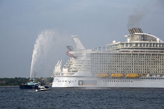 Harmony of the Seas world's largest cruise ship. Harmony of the Seas the worlds' largest cruise ship gets a traditional water spray send off from tug Lomax on Stock Images