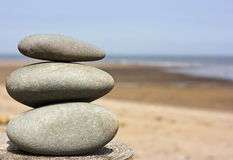 Harmony Stone Stack. Composition of pebble stacks resting on wooden post with beach background Stock Photo