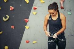 Harnais de dactylographie d'entraîneur de femme sur le mur s'élevant dans le gymnase photo libre de droits