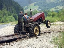 Harnessing a mechanical beast. Farm tractor hauling logs stock photos
