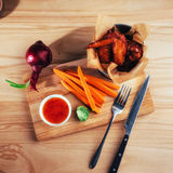 Harnished chicken wings with sauce and vegetables on wooden table Royalty Free Stock Photos