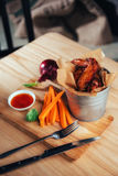 Harnished chicken wings with sauce and vegetables on wooden table Royalty Free Stock Photography