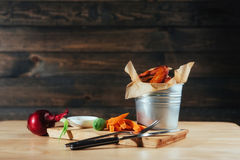 Harnished chicken wings with sauce and vegetables on wooden table Stock Photography