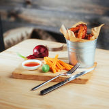 Harnished chicken wings with sauce and vegetables on wooden table Stock Image