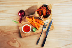 Harnished chicken wings with sauce and vegetables on wooden table Stock Photos