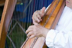Harp. A man playing the strings on a harp Stock Photos