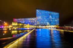 Harpa Concert Hall Iceland. Harpa concert hall in Iceland at night lights up in multiple colors, reflecting on a pool at the front of the building Royalty Free Stock Photos