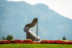 Harpaspringbrunnen i Ossiach, Österrike Skog och berg i bakgrunden arkivfoto