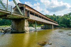 Over One Hundred Years Old. This is Harpersfield Covered Bridge that spans the Grand River in northeast Ohio the bridge is over a hundred years old and cars Stock Photos