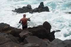 Harpoon spear fisherman at rocky shore royalty free stock image