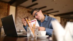 Harried handsome young businessman in glasses working on laptop, talking on phone, taking notes and searches info in. Harried handsome young businessman in stock video footage