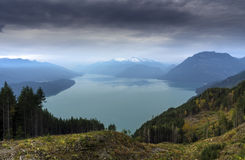 Harrison Bliss. Harrison Lake receives a sense of calm at sunset right before a storm moves in Stock Images