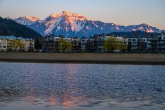 Harrison Hot Springs in Fraser Valley, British Columbia with the lagoon in the foreground and in the background, the snow-caped. The village of Harrison Hot royalty free stock photos