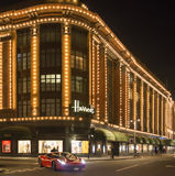 Harrods department store. Ferrari passes in front of the buildin Stock Photo