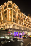 Harrods department store. Taxi passes in front of it Stock Photo