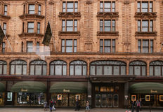 Harrods shopping mall. Harrods luxury shopping mass  in London, England in front view with passersby walking in May 16 2012 Royalty Free Stock Photos