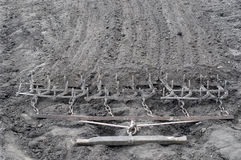 Harrow. Ancient iron plow on the earth. Stock Image