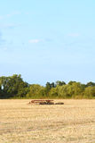 Harrow among the stubble on harvested farmland Royalty Free Stock Image