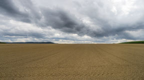 Harrowed field with dark clouds Stock Image