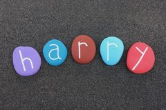 Harry, masculine given name with multicolored stones over black volcanic sand. Harry, masculine name celebrated with multicolored and carved stones over black Stock Photos
