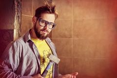 Harsh bearded workman in goggles tapping hammer on the palm with the intention of lather someone`s neck or crumble bull. Bearded workman in goggles tapping royalty free stock photo