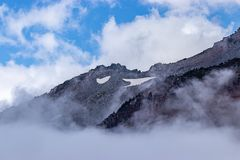 Harsh craggy mountaintop with clouds and fog. And banks of snow stock photography