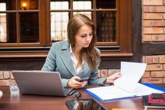 Hart arbeitend Geschäftsfrau im Restaurant mit Laptop und Handy. stockfotografie