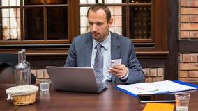 Hart arbeitend Geschäftsmann im Restaurant mit Laptop und Handy. stockfoto