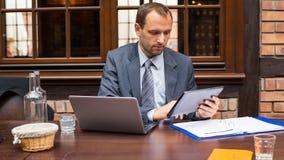 Hart arbeitend lächelnder Geschäftsmann im Restaurant mit Laptop und Auflage. stockfotografie