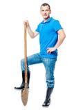 Hart arbeitend Landwirt mit einer Schaufel in voller Länge auf einem Weiß Lizenzfreie Stockfotos