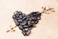 Hart dat met kiezelstenen op het zand wordt getrokken Stock Foto