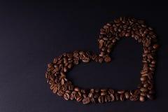 Hart dat met koffiebonen wordt gevoerd stock foto