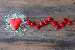 Hart gevormd chocoladesuikergoed met rood verpakkingsmateriaal stock foto's