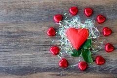 Hart gevormd chocoladesuikergoed met rood verpakkingsmateriaal royalty-vrije stock afbeelding