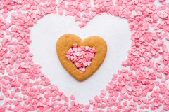 Hart gevormd die koekje met roze suikergoedharten wordt omringd stock foto's