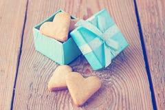 Hart gevormde koekjes in een blauwe giftdoos op een houten achtergrond Stock Afbeelding